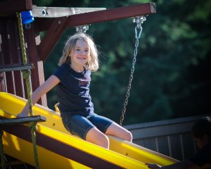 little girl on yellow slide
