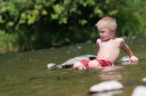 kid sitting in river