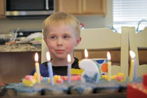 boy behind birthday cake candles